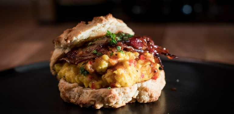 Scones topped with scrambled eggs and bacon