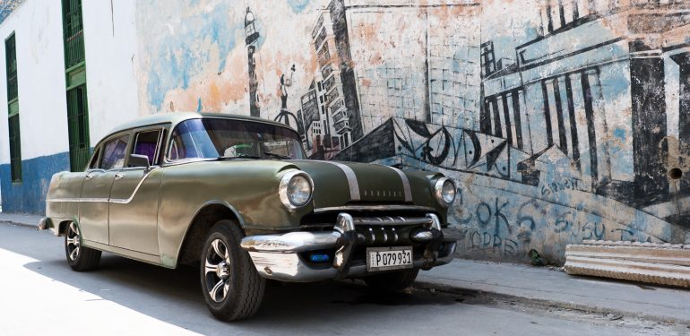 50's car in front of mural in Havana
